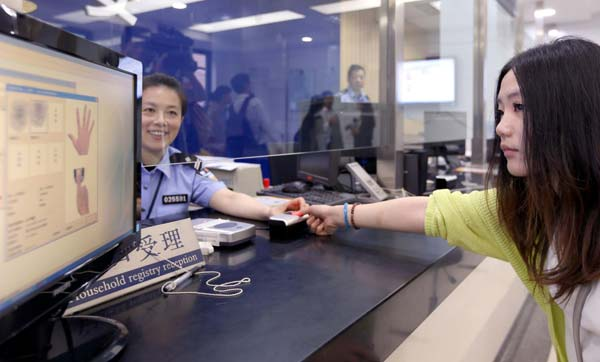 A Chinese girl who is scanning her fingerprints when applying a new China Resident Identity Card.