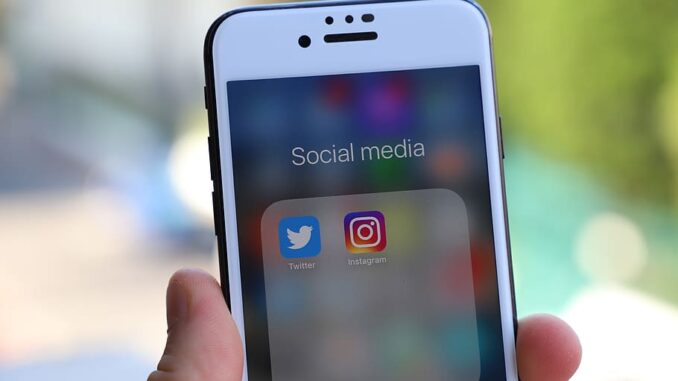 Person holding phone with social media folder open